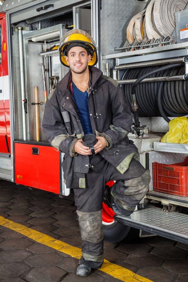 Χαμογελώντας πυροσβέστης που υπερασπίζεται το φορτηγό στο πυροσβεστικό σταθμό στοκ εικόνα με δικαίωμα ελεύθερης χρήσης