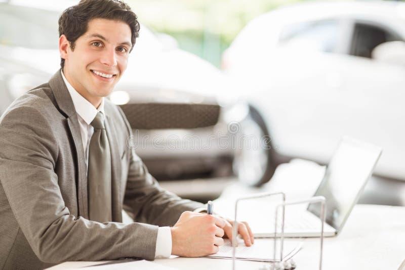 Χαμογελώντας πωλητής στο γραφείο του στοκ εικόνες
