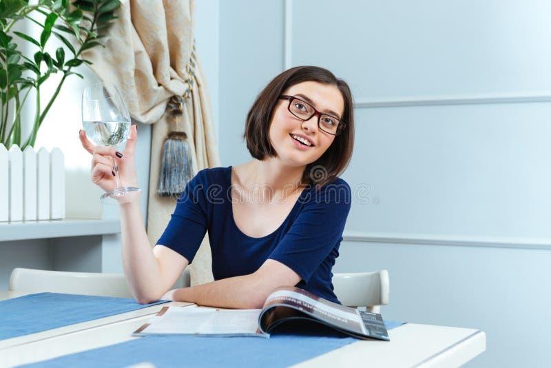 Χαμογελώντας πόσιμο νερό γυναικών και αναμονή τη σερβιτόρα στον καφέ στοκ εικόνες