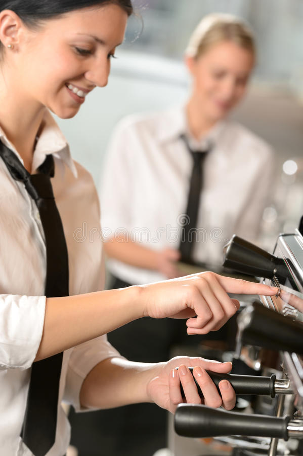 Χαμογελώντας σερβιτόρα γυναικών που προετοιμάζει τη μηχανή καφέ στοκ εικόνα