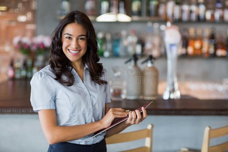 Χαμογελώντας σερβιτόρα που κρατά ένα αρχείο στοκ εικόνες με δικαίωμα ελεύθερης χρήσης