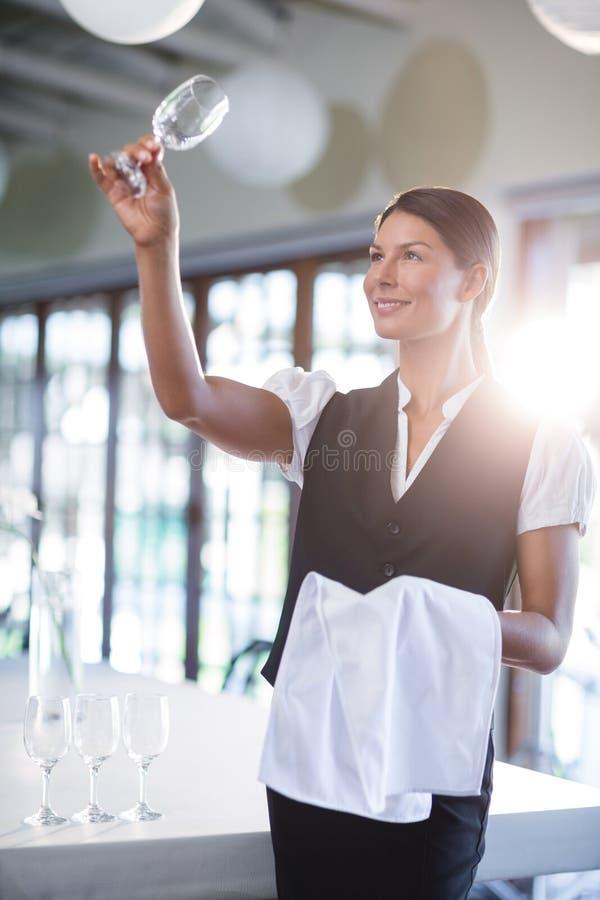 Χαμογελώντας σερβιτόρα που κρατά ψηλά ένα κενό γυαλί κρασιού στοκ εικόνες