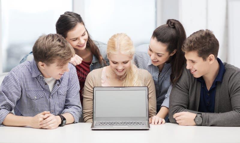 Χαμογελώντας σπουδαστές που εξετάζουν την κενή οθόνη lapotop στοκ εικόνα