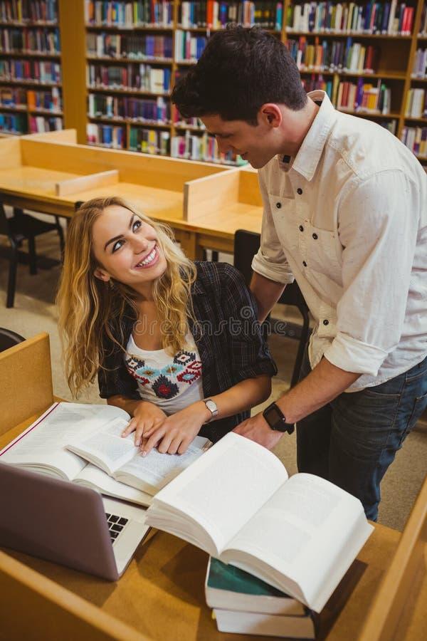 Χαμογελώντας σπουδαστές που εργάζονται μαζί καθμένος στον πίνακα στοκ φωτογραφίες
