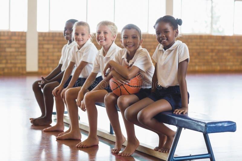 Χαμογελώντας σπουδαστές που κάθονται στον πάγκο με την καλαθοσφαίριση στοκ εικόνα με δικαίωμα ελεύθερης χρήσης