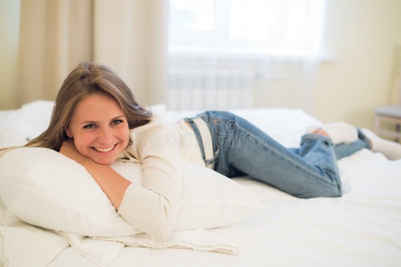 Χαμογελώντας στοχαστική όμορφη γυναίκα που βρίσκεται στο κρεβάτι στο σπίτι στοκ εικόνα με δικαίωμα ελεύθερης χρήσης