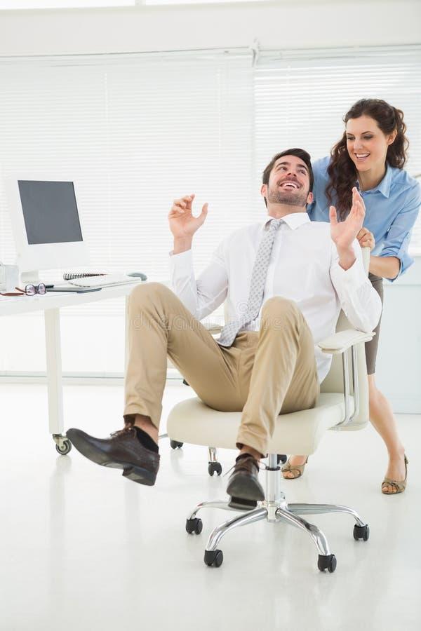 Χαμογελώντας συνεργάτες που παίζουν μαζί με την καρέκλα στροφέων στοκ φωτογραφία