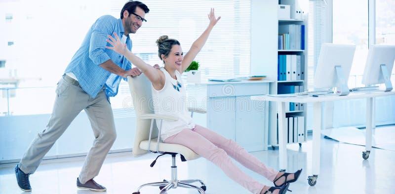 Χαμογελώντας συντάκτες φωτογραφιών που έχουν τη διασκέδαση με σε μια καρέκλα στροφέων στοκ φωτογραφία με δικαίωμα ελεύθερης χρήσης