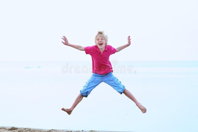 Χαμογελώντας σχολικό αγόρι που πηδά στην παραλία στοκ φωτογραφία με δικαίωμα ελεύθερης χρήσης