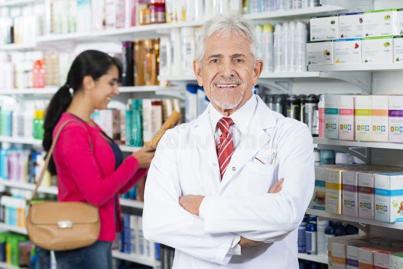 Χαμογελώντας τα μόνιμα όπλα φαρμακοποιών που διασχίζονται ενώ πελάτης που επιλέγει τις δημόσιες σχέσεις στοκ εικόνες με δικαίωμα ελεύθερης χρήσης