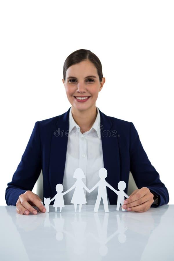 Χαμογελώντας το έγγραφο εκμετάλλευσης επιχειρηματιών που αποκόπτει της οικογένειας στοκ φωτογραφία