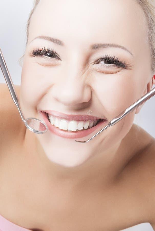Χαμογελώντας υγιής γυναίκα με τον καθρέφτη και Spatula οδοντιάτρων στοκ φωτογραφίες με δικαίωμα ελεύθερης χρήσης