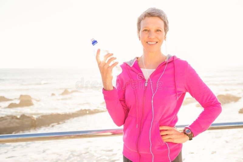 Χαμογελώντας φίλαθλη γυναίκα με τα ακουστικά που κρατά το μπουκάλι στοκ εικόνες με δικαίωμα ελεύθερης χρήσης