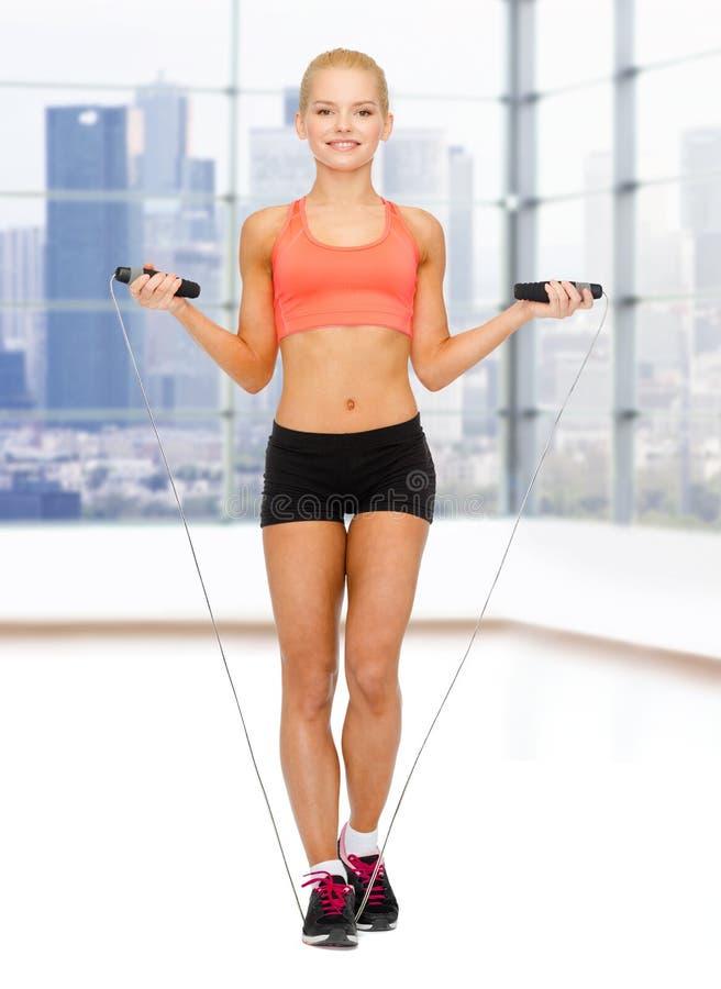 Χαμογελώντας φίλαθλη γυναίκα που πηδά με το πηδώντας σχοινί στοκ εικόνα με δικαίωμα ελεύθερης χρήσης