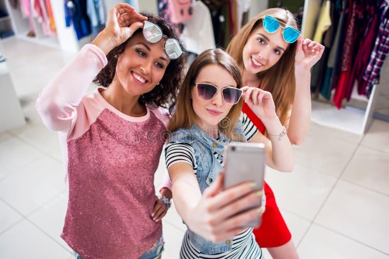 Χαμογελώντας φίλες που φορούν τα μοντέρνα γυαλιά ηλίου που έχουν το χρόνο διασκέδασης που παίρνει selfie με το κινητό τηλέφωνο κά στοκ φωτογραφίες με δικαίωμα ελεύθερης χρήσης