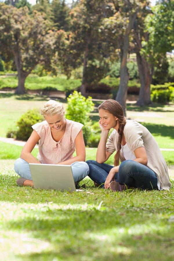 Χαμογελώντας φίλοι με μια συνεδρίαση lap-top στο χορτοτάπητα στοκ εικόνα