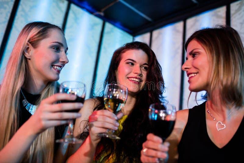 Χαμογελώντας φίλοι που απολαμβάνουν ενώ έχοντας το κρασί στοκ εικόνες