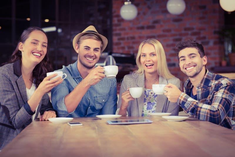Χαμογελώντας φίλοι που απολαμβάνουν τον καφέ από κοινού στοκ φωτογραφία με δικαίωμα ελεύθερης χρήσης
