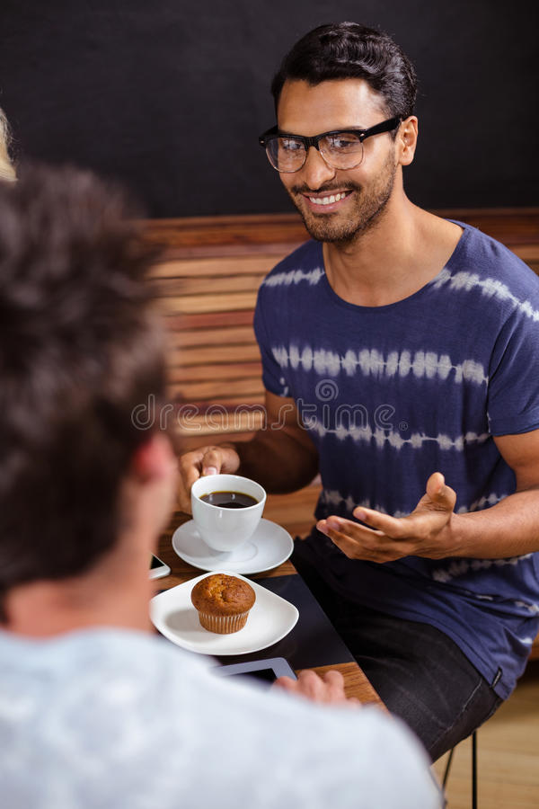 Χαμογελώντας φίλοι που απολαμβάνουν τον καφέ από κοινού στοκ φωτογραφίες