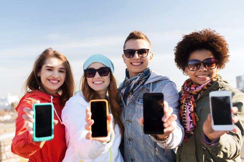Χαμογελώντας φίλοι που παρουσιάζουν κενές οθόνες smartphone στοκ εικόνες