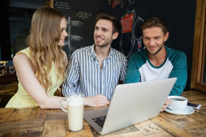 Χαμογελώντας φίλοι που χρησιμοποιούν το lap-top καθμένος στον πίνακα στοκ εικόνα με δικαίωμα ελεύθερης χρήσης