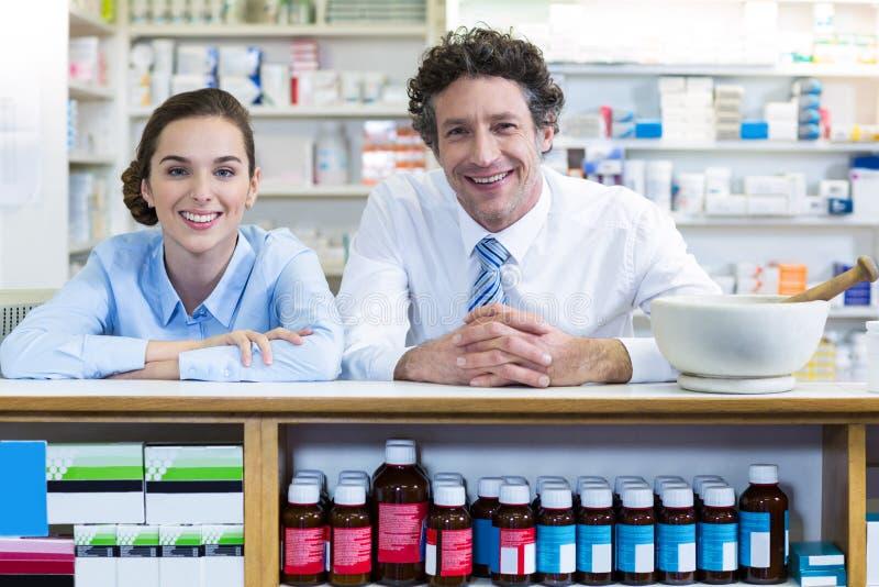 Χαμογελώντας φαρμακοποιοί που κλίνουν στο μετρητή στο φαρμακείο στοκ φωτογραφίες