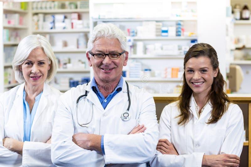 Χαμογελώντας φαρμακοποιοί που στέκονται με τα όπλα που διασχίζονται στο φαρμακείο στοκ φωτογραφίες