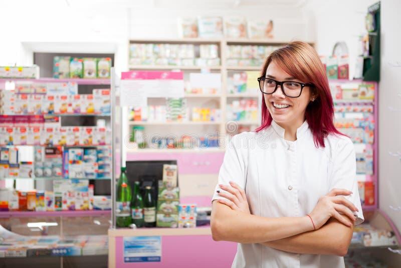 Χαμογελώντας φαρμακοποιός γυναικών μπροστά από το γραφείο στοκ εικόνα με δικαίωμα ελεύθερης χρήσης