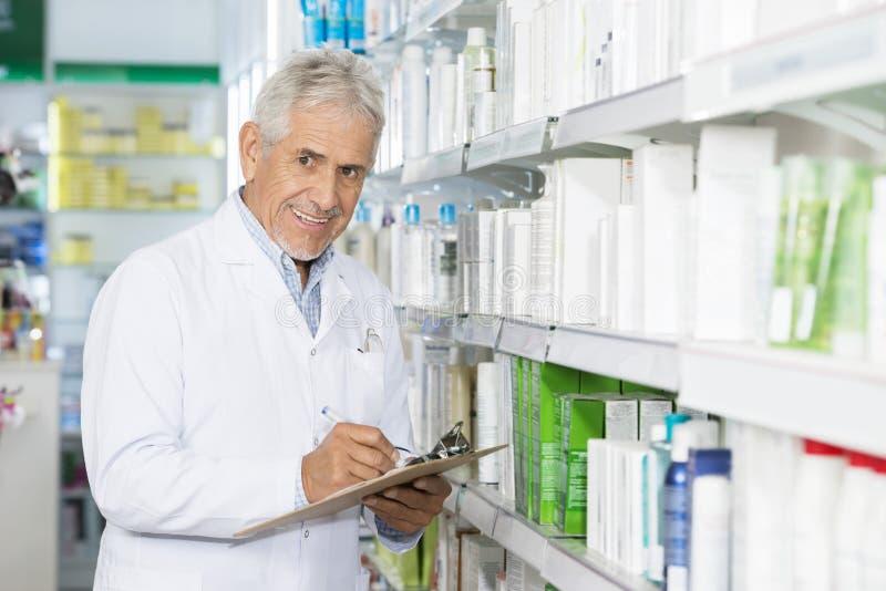 Χαμογελώντας φαρμακοποιός που γράφει στην περιοχή αποκομμάτων υπερασπιμένος τα ράφια στοκ εικόνα