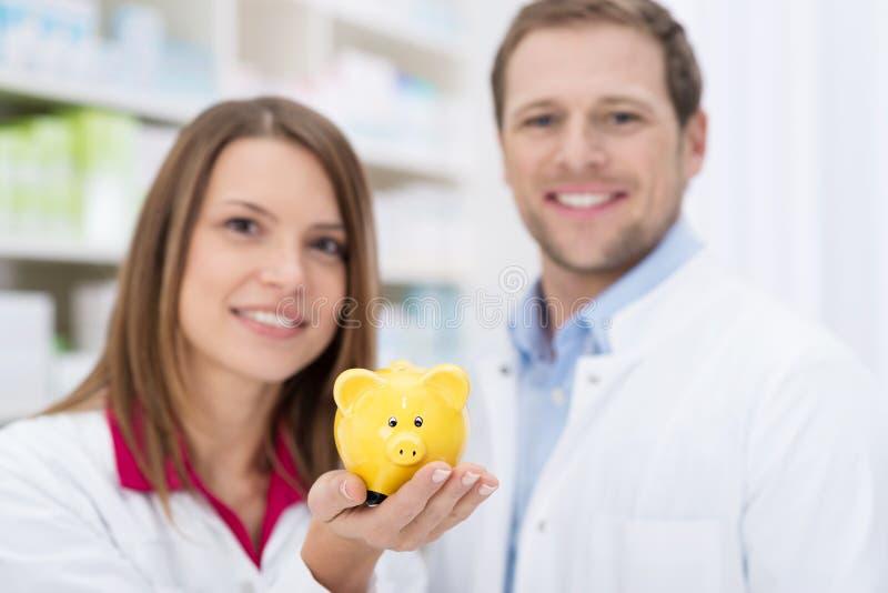 Χαμογελώντας φαρμακοποιός που κρατά ψηλά μια piggy τράπεζα στοκ φωτογραφία
