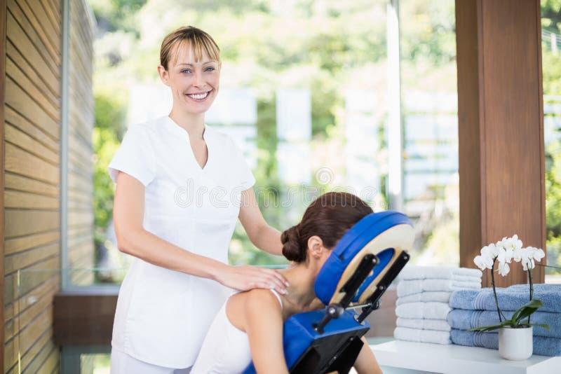 Χαμογελώντας φυσιοθεραπευτής που δίνει το μασάζ ώμων στη γυναίκα στοκ εικόνα