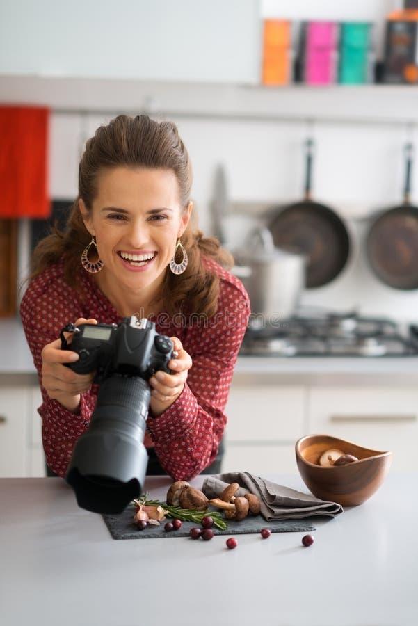 Χαμογελώντας φωτογράφος τροφίμων γυναικών που ανατρέχει από τα τρόφιμα στοκ εικόνα