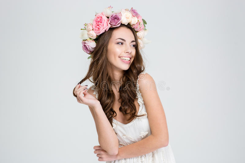 Χαμογελώντας χαριτωμένη γυναίκα με το στεφάνι των τριαντάφυλλων στοκ φωτογραφία