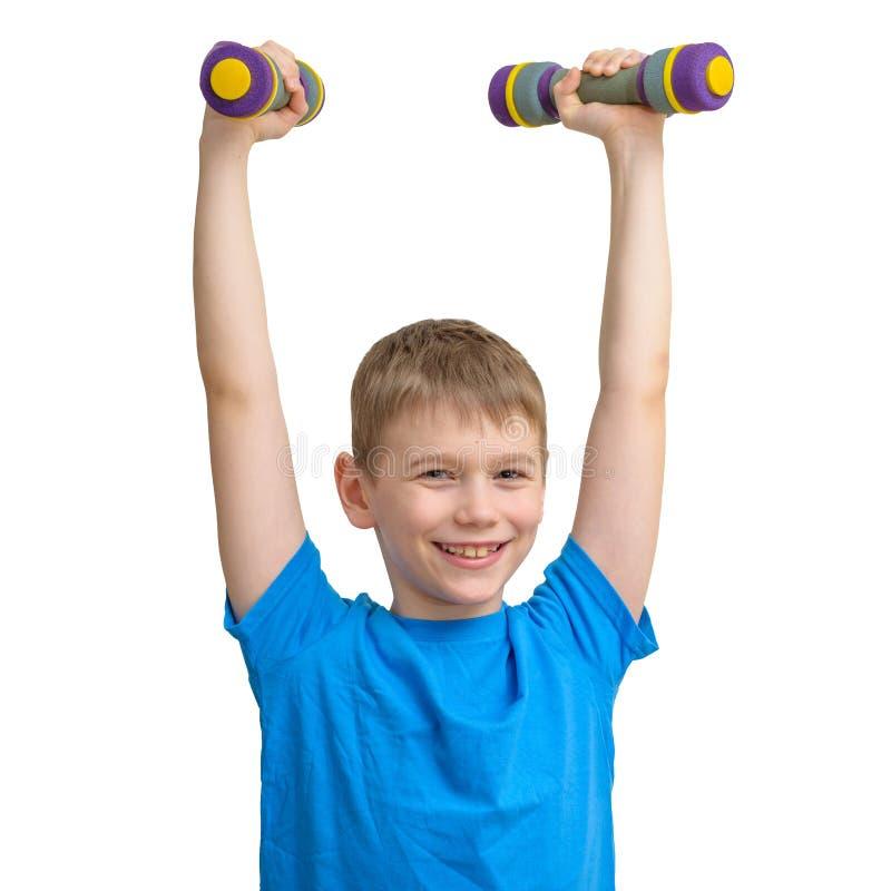 Χαμογελώντας χαριτωμένο αθλητικό αγόρι που ασκεί με τους αλτήρες που απομονώνονται στο λευκό στοκ φωτογραφίες