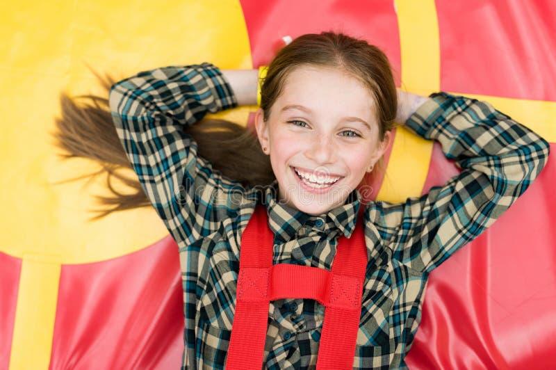 Χαμογελώντας χαρούμενο κορίτσι που βρίσκεται στο τραμπολίνο στοκ φωτογραφίες