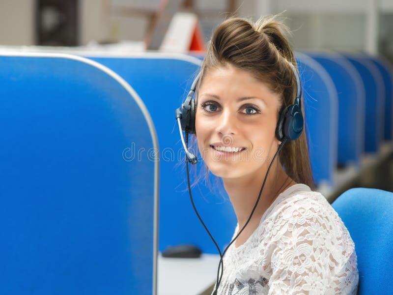 Χαμογελώντας χειριστής στο τηλεφωνικό κέντρο στοκ εικόνα
