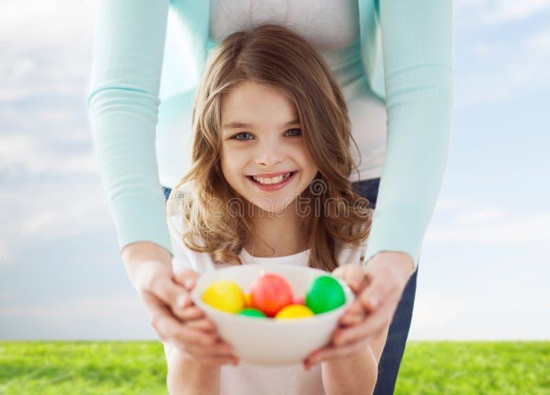 Χαμογελώντας χρωματισμένα εκμετάλλευση αυγά κοριτσιών και μητέρων στοκ εικόνα