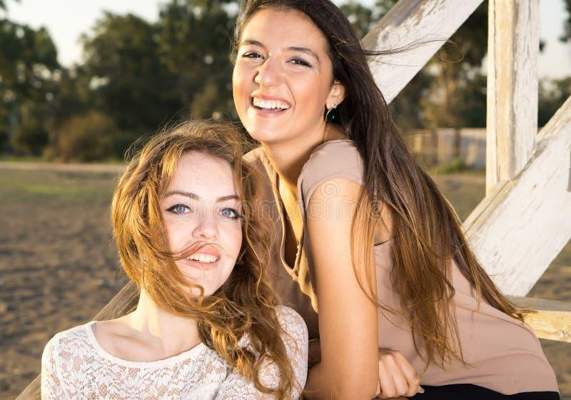 Χαμογελώντας όμορφα κορίτσια σε ένα θυελλώδες απόγευμα στοκ εικόνες