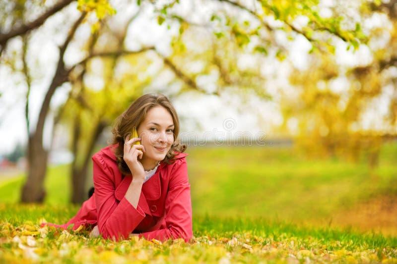 Χαμογελώντας όμορφη γυναίκα που μιλά στο τηλέφωνο στοκ φωτογραφία
