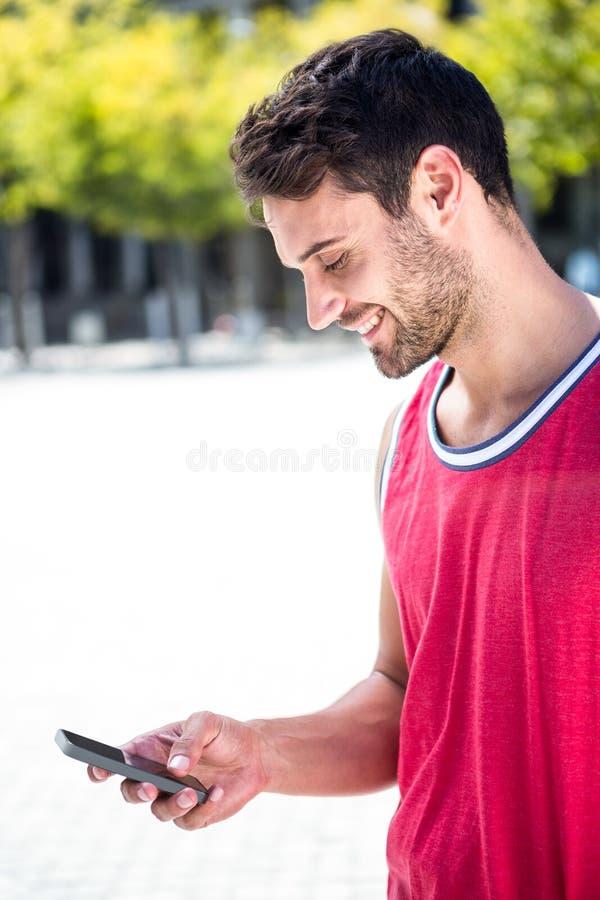Χαμογελώντας όμορφος αθλητής που στέλνει ένα κείμενο στοκ φωτογραφία με δικαίωμα ελεύθερης χρήσης