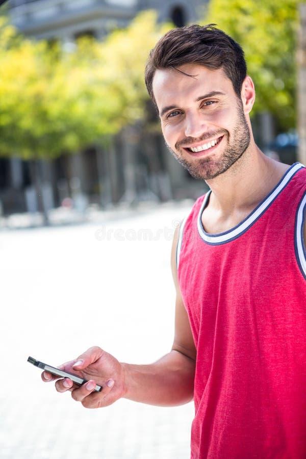 Χαμογελώντας όμορφος αθλητής που στέλνει ένα κείμενο στοκ φωτογραφία