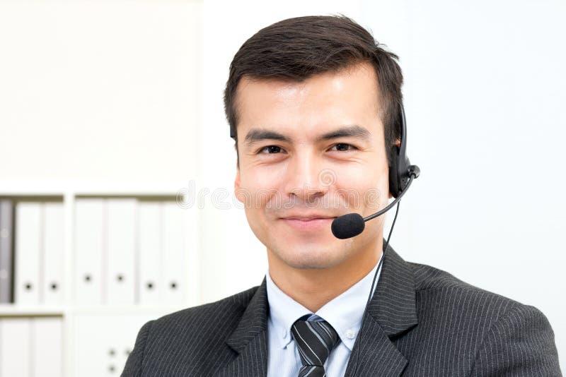 Χαμογελώντας όμορφος επιχειρηματίας που φορά την κάσκα μικροφώνων στοκ φωτογραφία