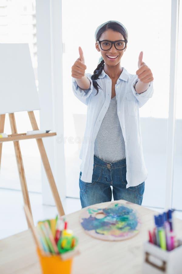 Χαμογελώντας όμορφος καλλιτέχνης που δίνει τους αντίχειρες μέχρι τη κάμερα στοκ φωτογραφία με δικαίωμα ελεύθερης χρήσης