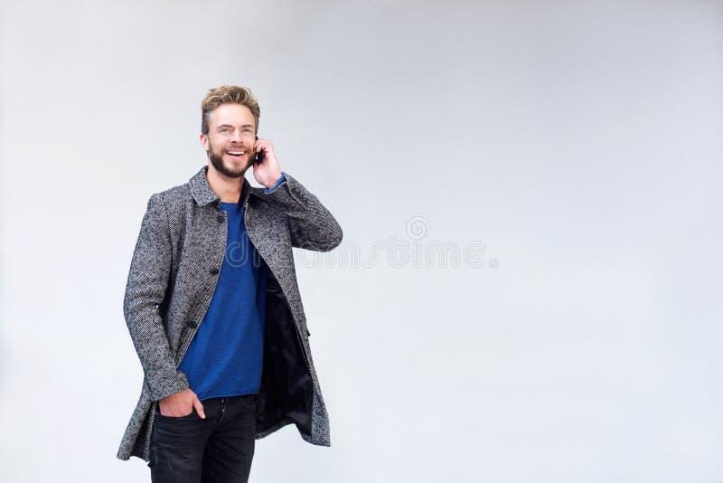 Χαμογελώντας όμορφο άτομο που ακούει το τηλέφωνο κυττάρων στοκ φωτογραφίες