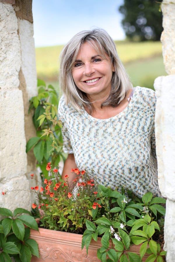 Χαμογελώντας ώριμη γυναίκα που στέκεται στον κήπο στοκ εικόνες