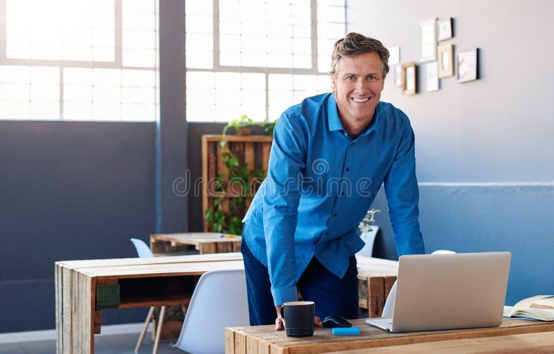 Χαμογελώντας ώριμος επιχειρηματίας που κλίνει στο γραφείο του σε ένα γραφείο στοκ φωτογραφία με δικαίωμα ελεύθερης χρήσης
