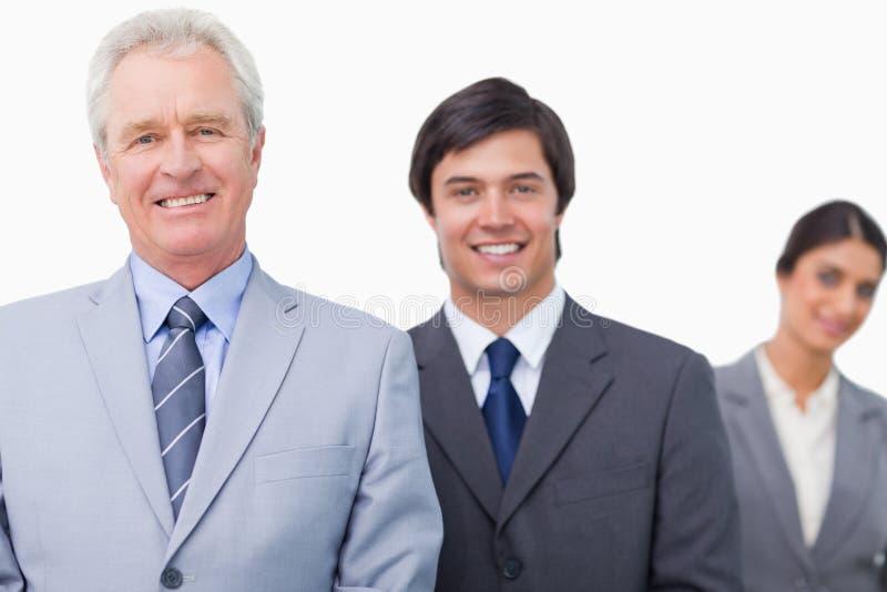 Χαμογελώντας ώριμος πωλητής με τους υπαλλήλους του στοκ εικόνα