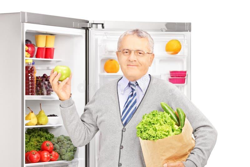 Χαμογελώντας ώριμο άτομο που κρατά μια τσάντα εγγράφου δίπλα σε ένα ψυγείο στοκ φωτογραφίες