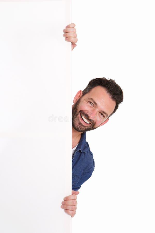 Χαμογελώντας ώριμο άτομο που κρυφοκοιτάζει πέρα από το κενό σημάδι αφισών στοκ εικόνα με δικαίωμα ελεύθερης χρήσης
