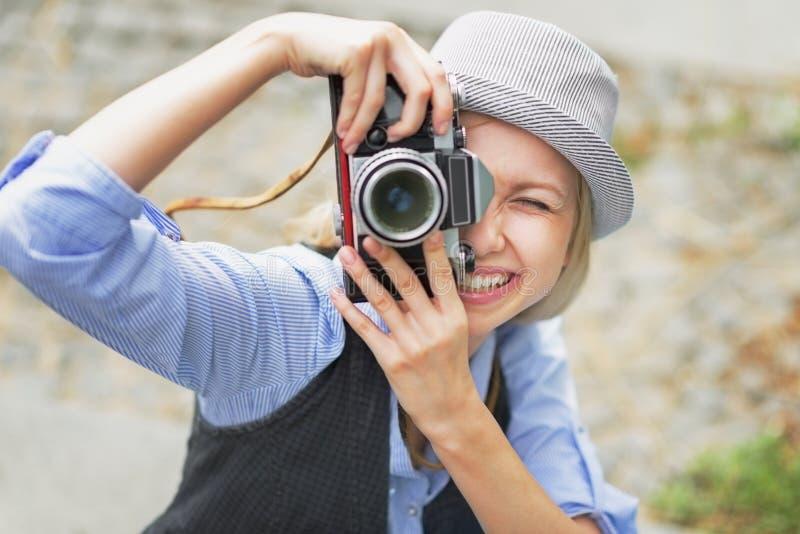 Χαμογελώντας hipster κορίτσι που κάνει τη φωτογραφία με την αναδρομική κάμερα στοκ εικόνα με δικαίωμα ελεύθερης χρήσης